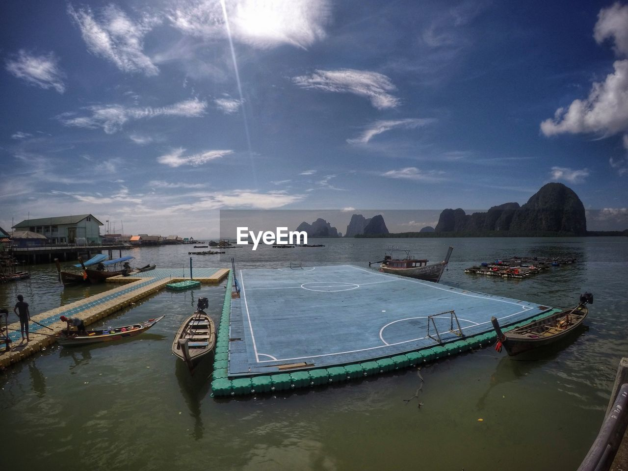 Floating Platform And Boats In Sea Against Sky During Sunny Day