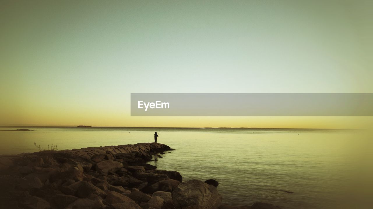 water, sea, scenics, tranquil scene, nature, beauty in nature, tranquility, sunset, rock - object, horizon over water, copy space, idyllic, outdoors, clear sky, sky, no people, beach, groyne, day