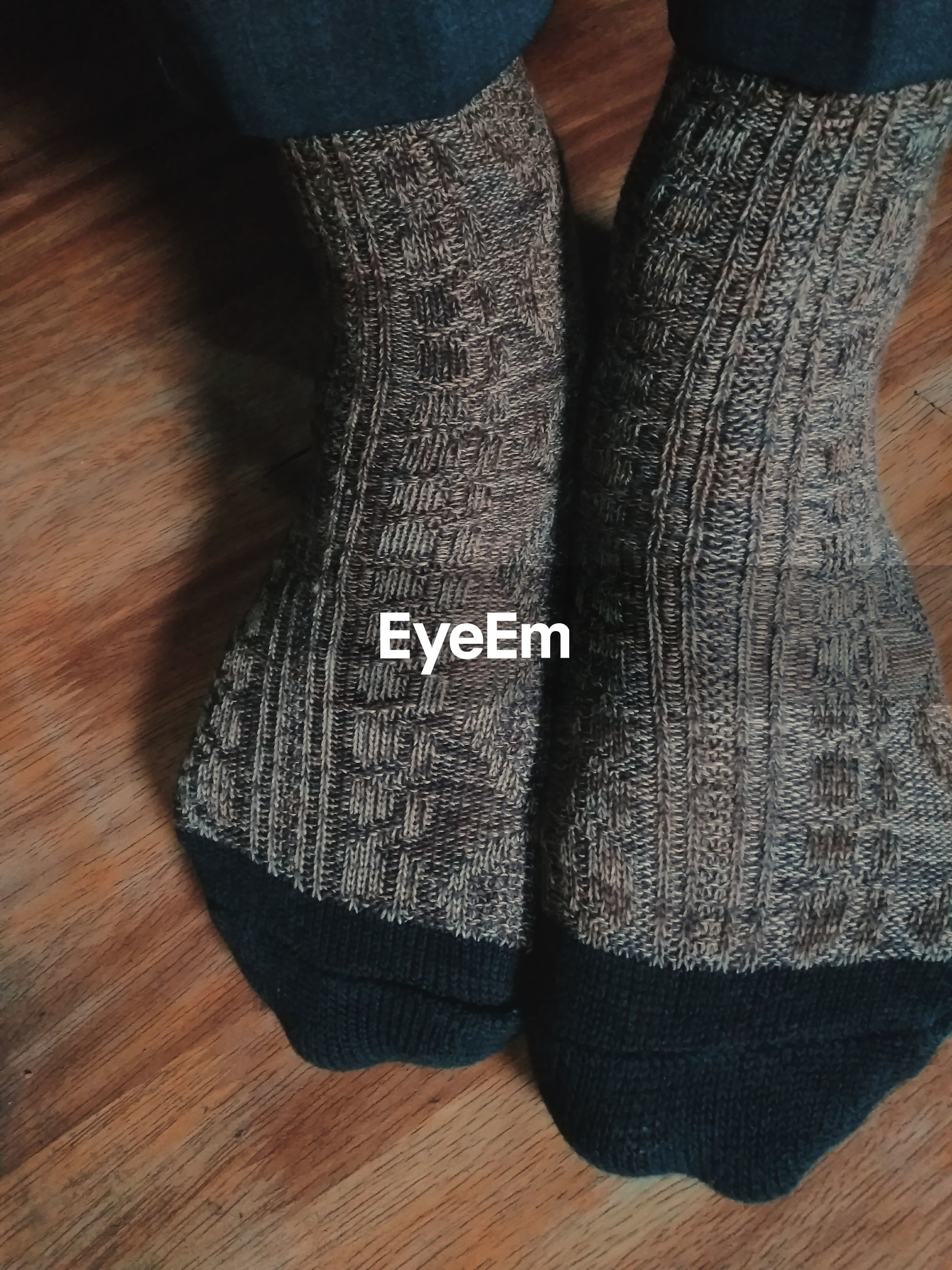 Low section of person wearing socks on hardwood floor