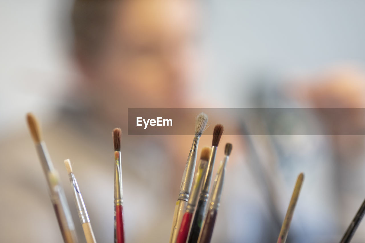 close-up, focus on foreground, selective focus, brush, paintbrush, art and craft, creativity, indoors, incense, large group of objects, still life, craft, day, people, built structure, skill, belief, art and craft equipment