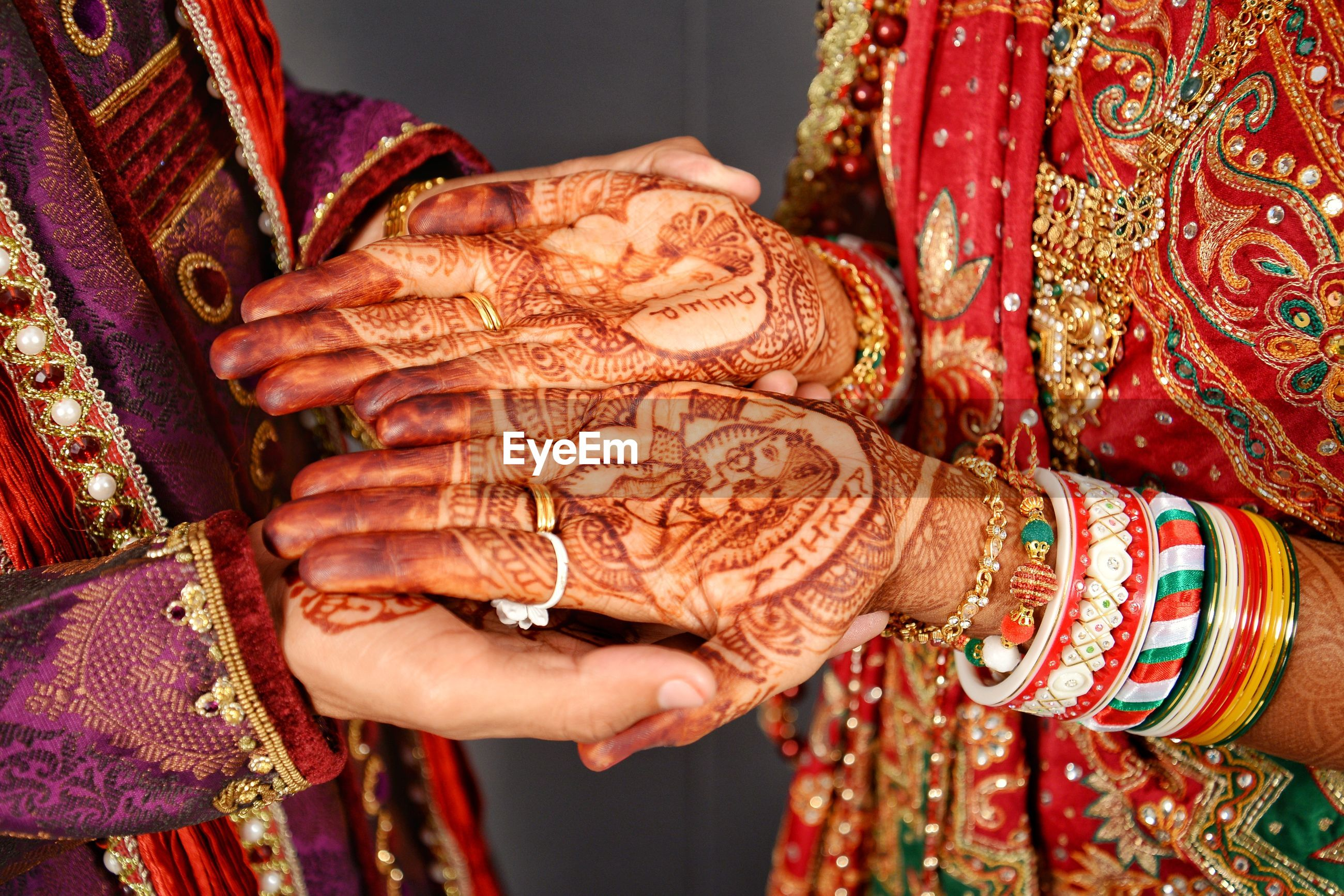 Midsection of groom holding bride hands with henna tattoo