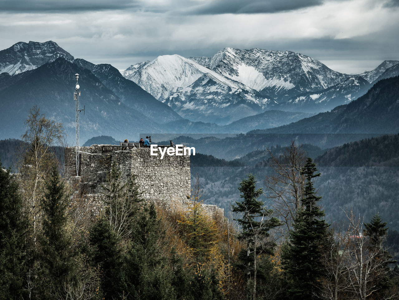 Castle Against Snowcapped Mountains During Foggy Weather