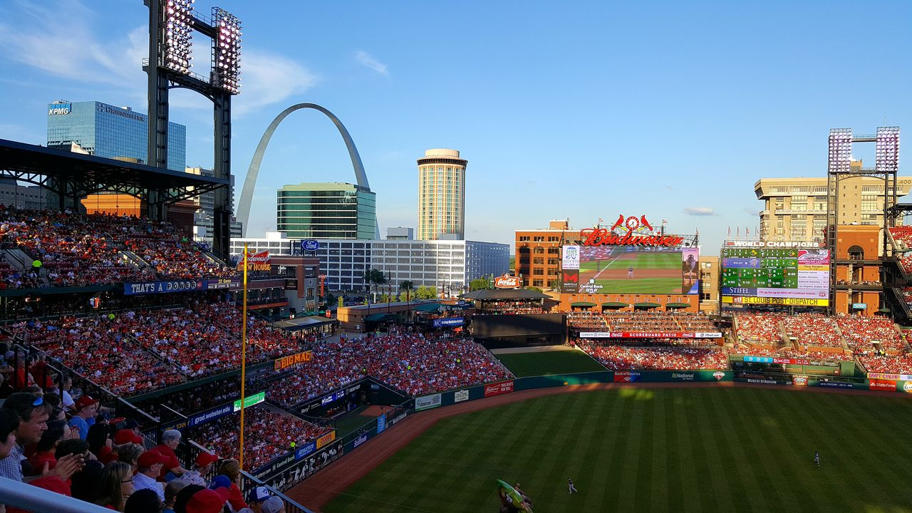 architecture, city, outdoors, building exterior, day, built structure, skyscraper, crowd, large group of people, sky, stadium, cityscape