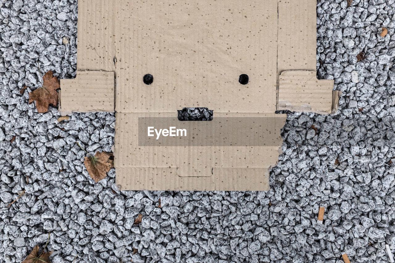 High Angle View Of Cardboard Box On Stones