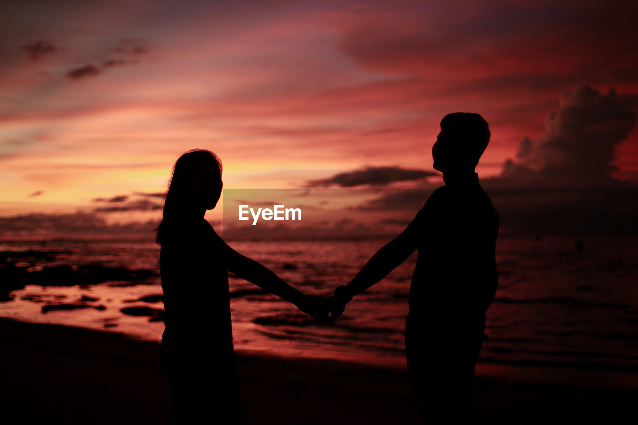 Silhouette couple holding hands while standing on beach during sunset