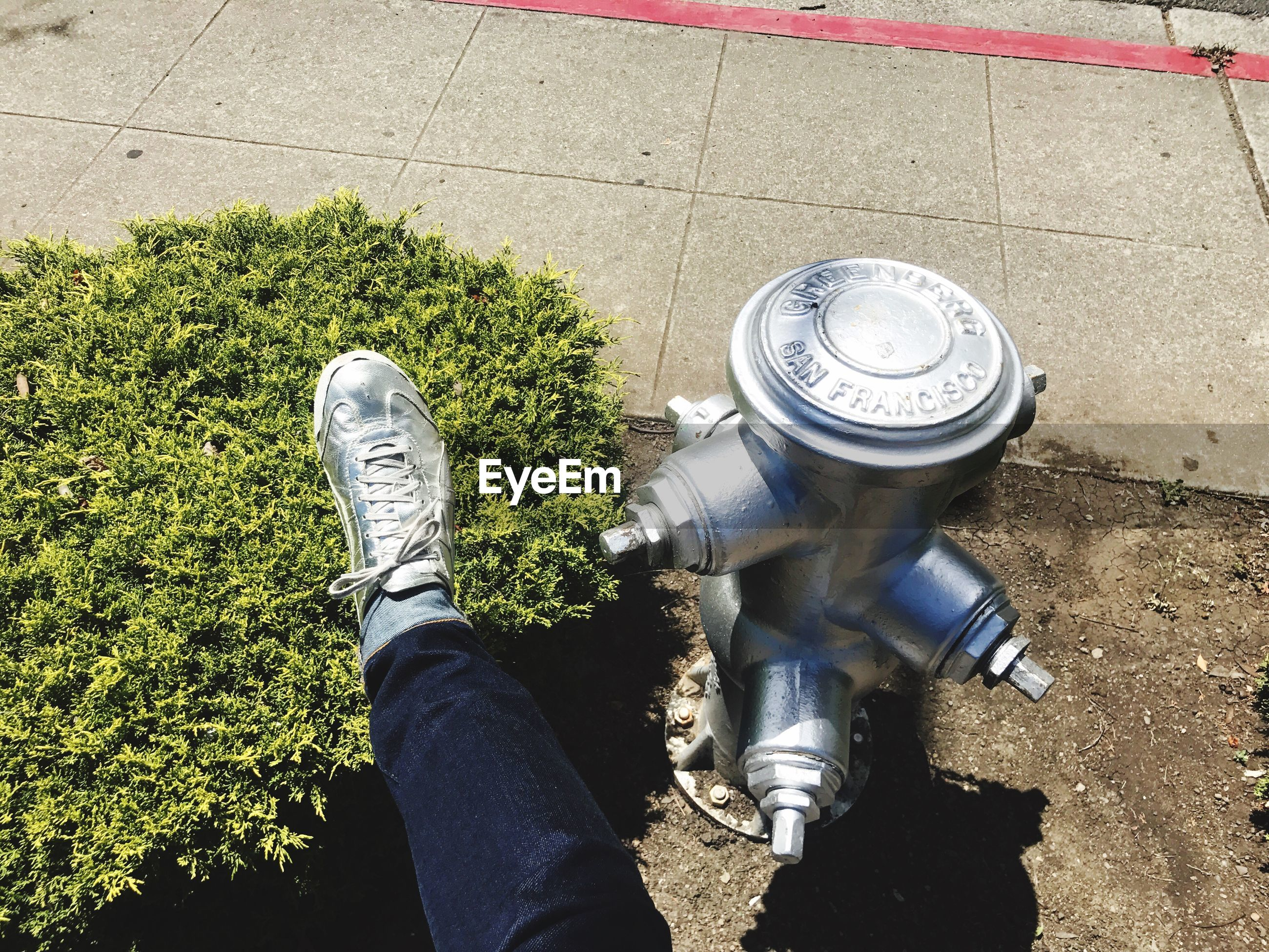 Low section of person wearing silver shoe by fire hydrant at sidewalk