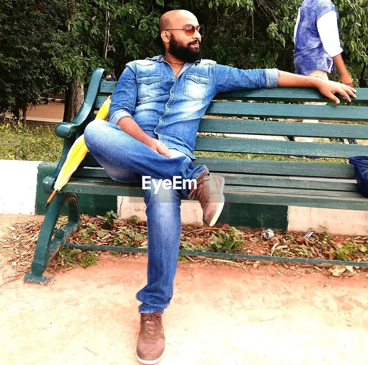 Man Sitting On Wooden Bench At Park