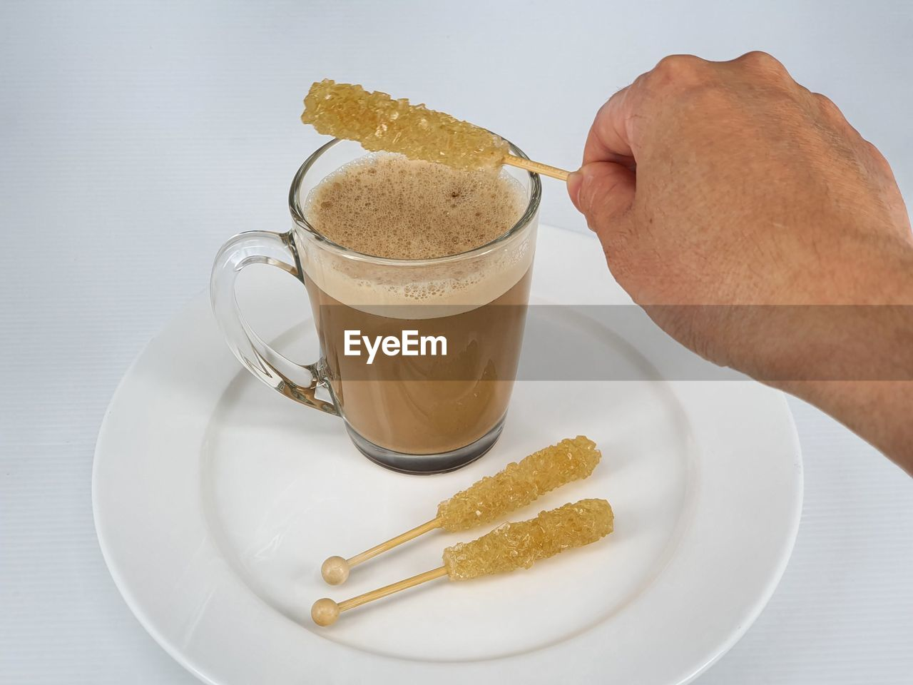 HIGH ANGLE VIEW OF HAND HOLDING COFFEE CUP AND DRINK