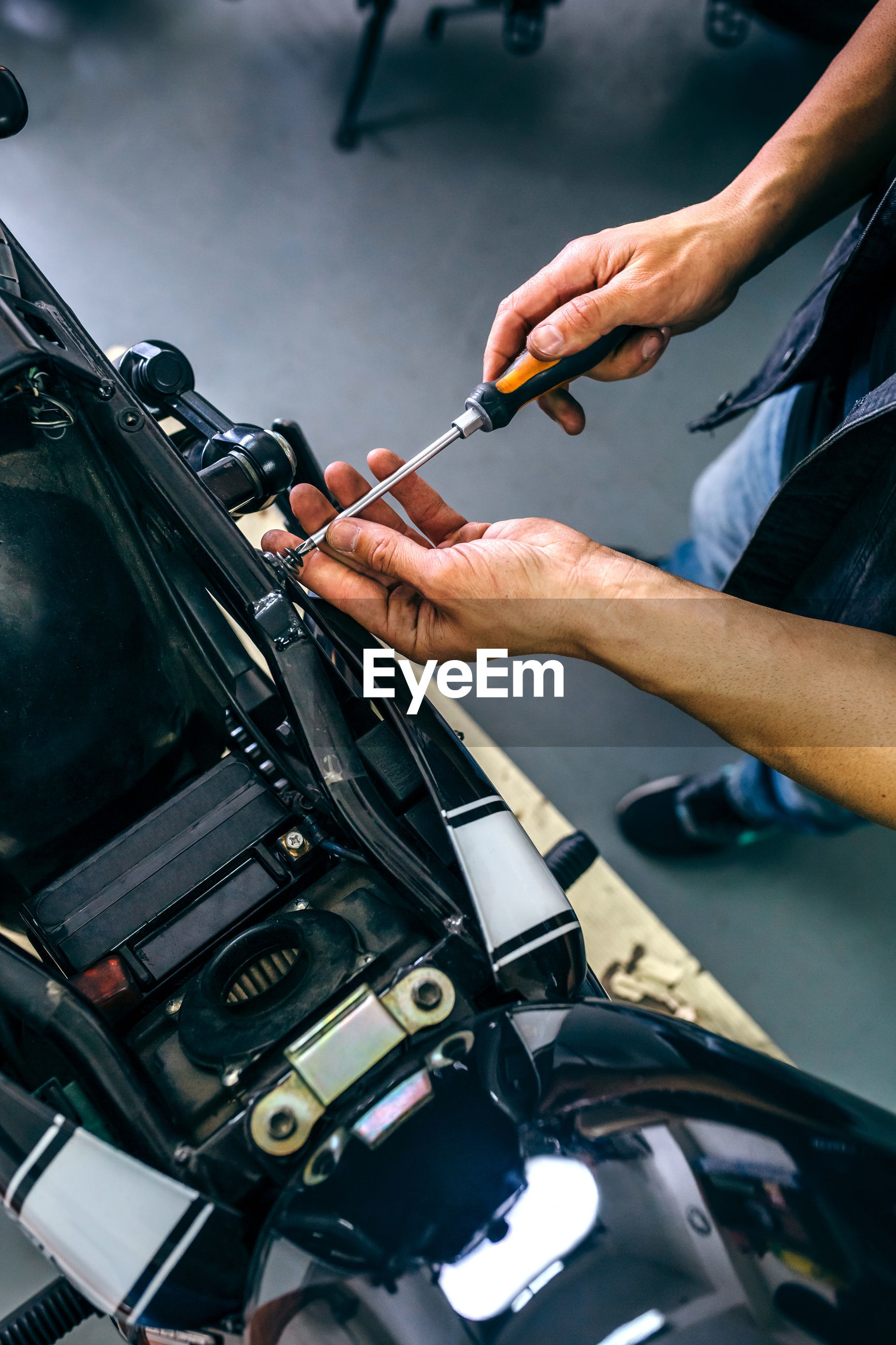 Low section of mature mechanic repairing motorcycle in garage