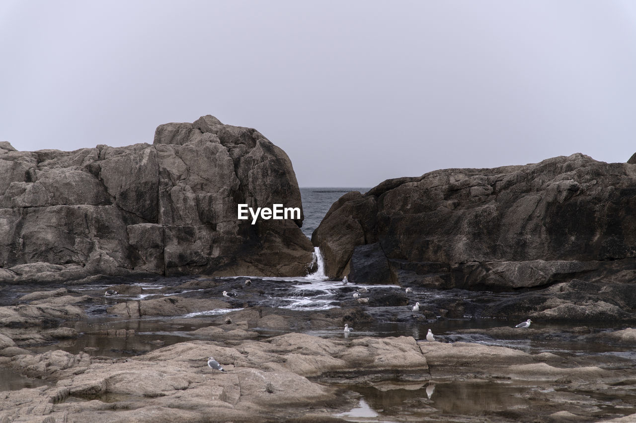 rock, sky, water, rock - object, solid, sea, rock formation, nature, clear sky, beauty in nature, land, no people, beach, copy space, cliff, tranquility, scenics - nature, tranquil scene, day, outdoors, eroded