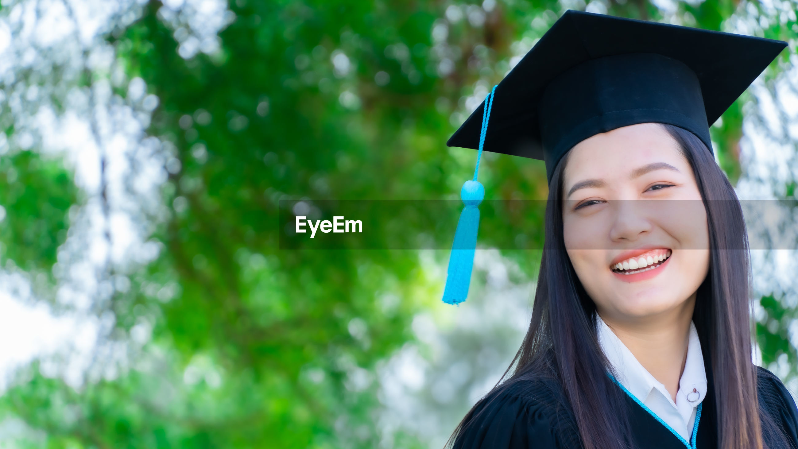 Portrait of smiling young woman wearing graduation gown while standing outdoors