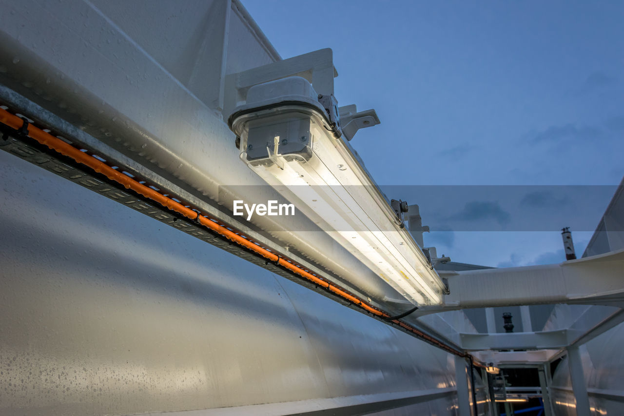 Low angle view illuminated fluorescent lights against sky in ship