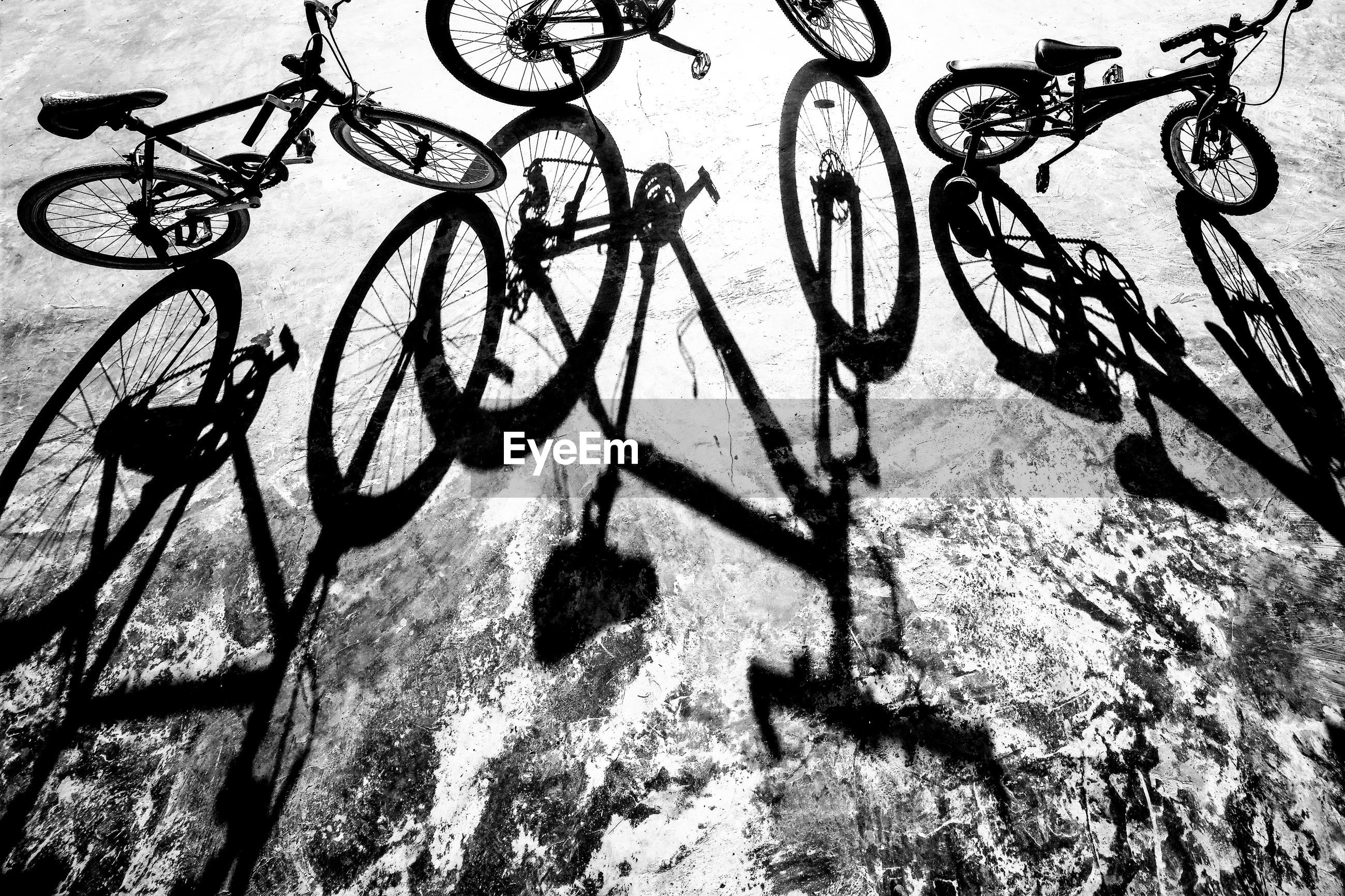 HIGH ANGLE VIEW OF BICYCLES ON FOOTPATH