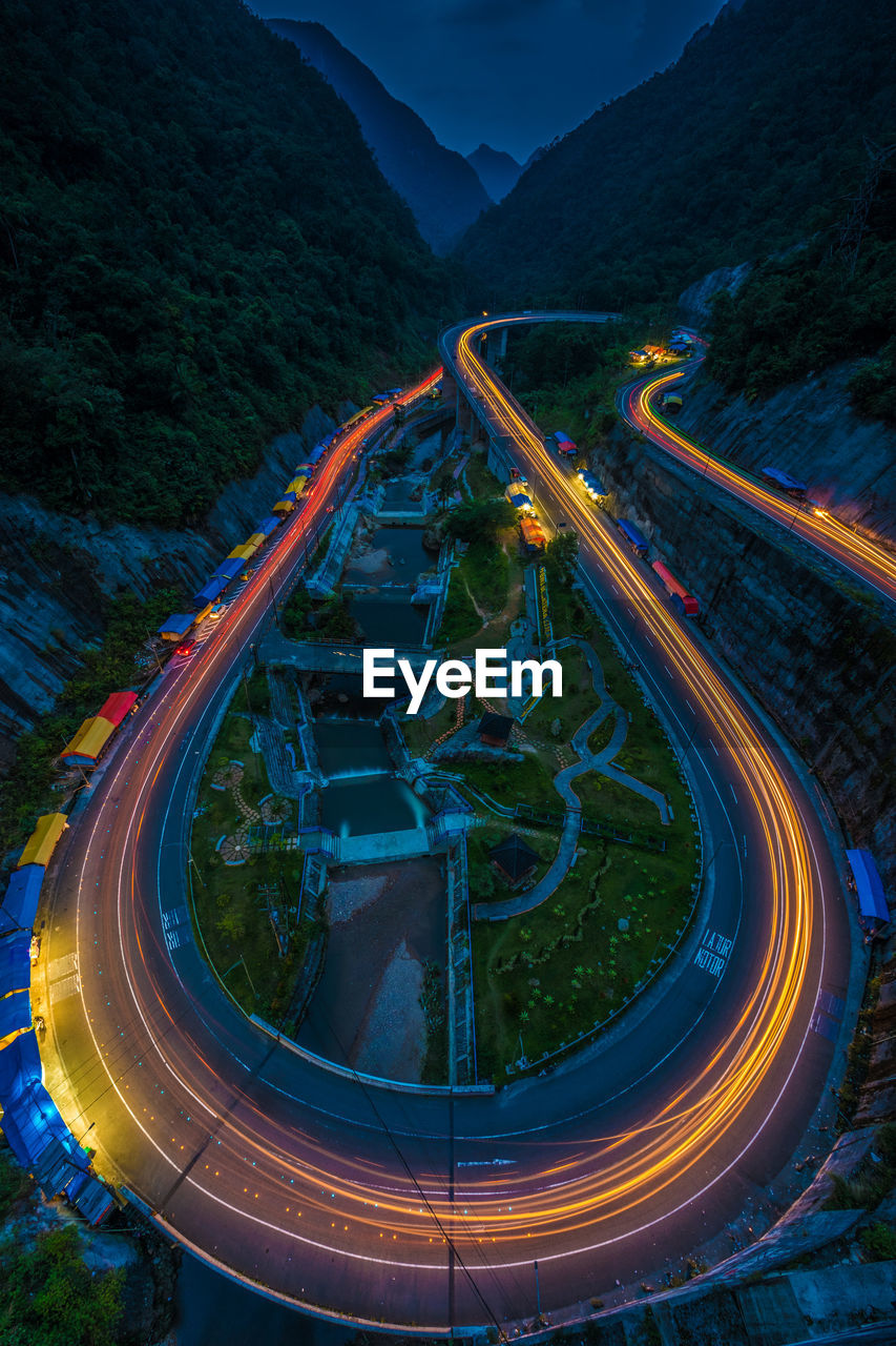 mountain, illuminated, road, transportation, speed, no people, long exposure, high angle view, nature, light trail, motion, night, mountain range, curve, highway, connection, architecture, water, blurred motion, street, outdoors