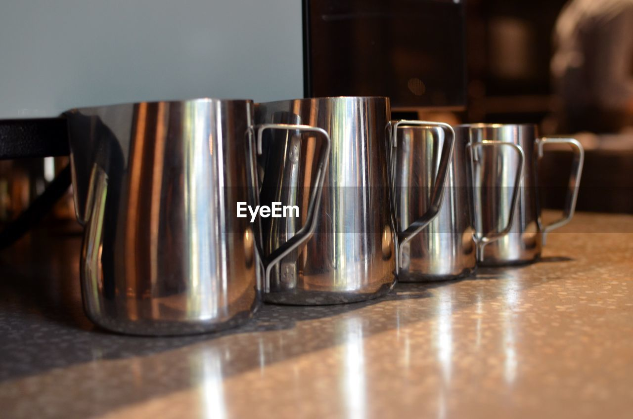 table, indoors, coffee, close-up, still life, metal, coffee - drink, side by side, selective focus, no people, mug, reflection, cup, food and drink, arrangement, wood - material, in a row, cafe, group of objects, coffee cup, steel, silver colored, coffee shop