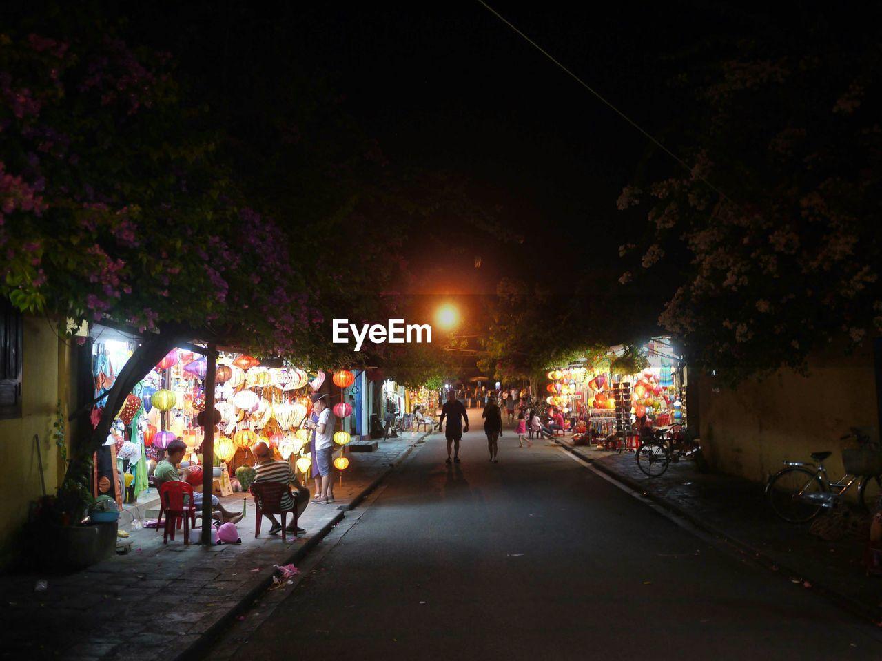 Man And Woman Walking At Street Market In Night