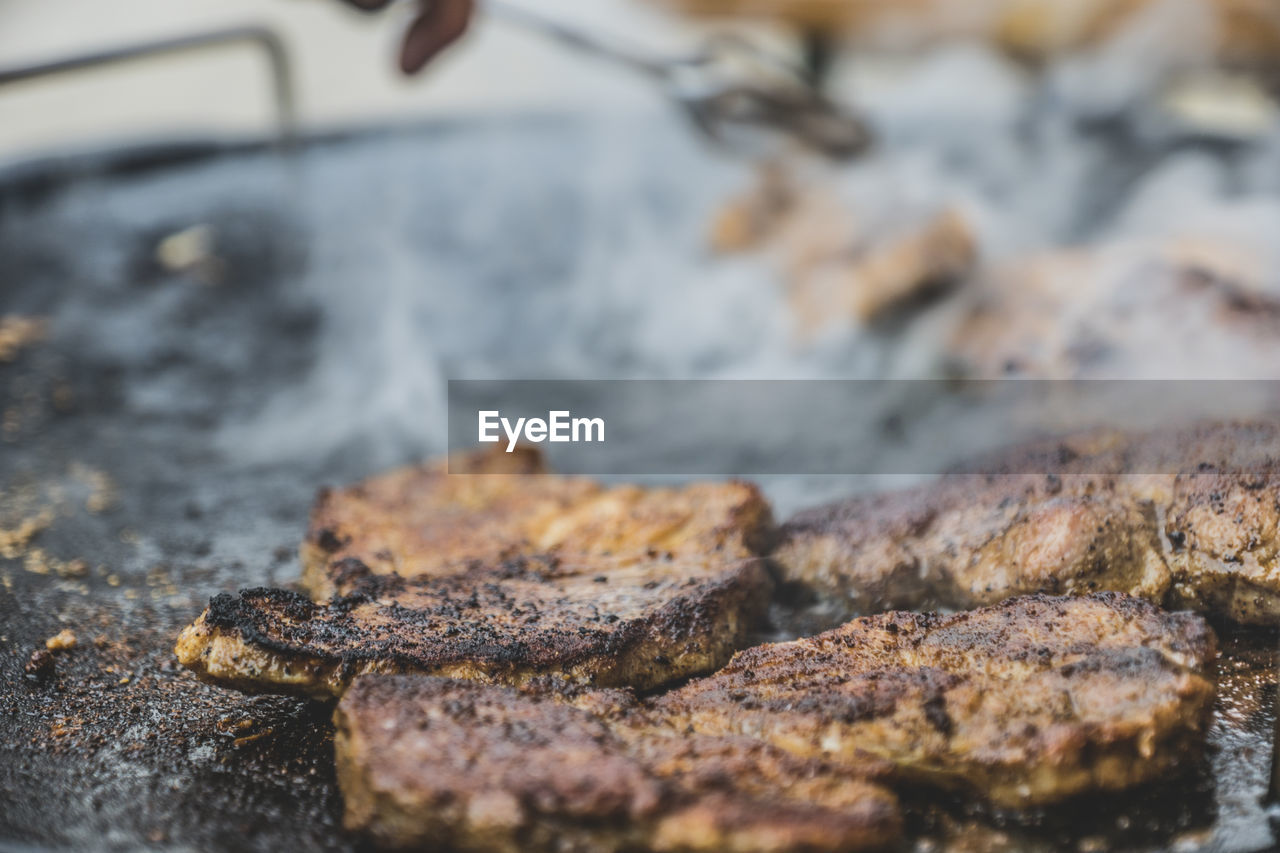 Close-Up Of Steak Frying In Pan