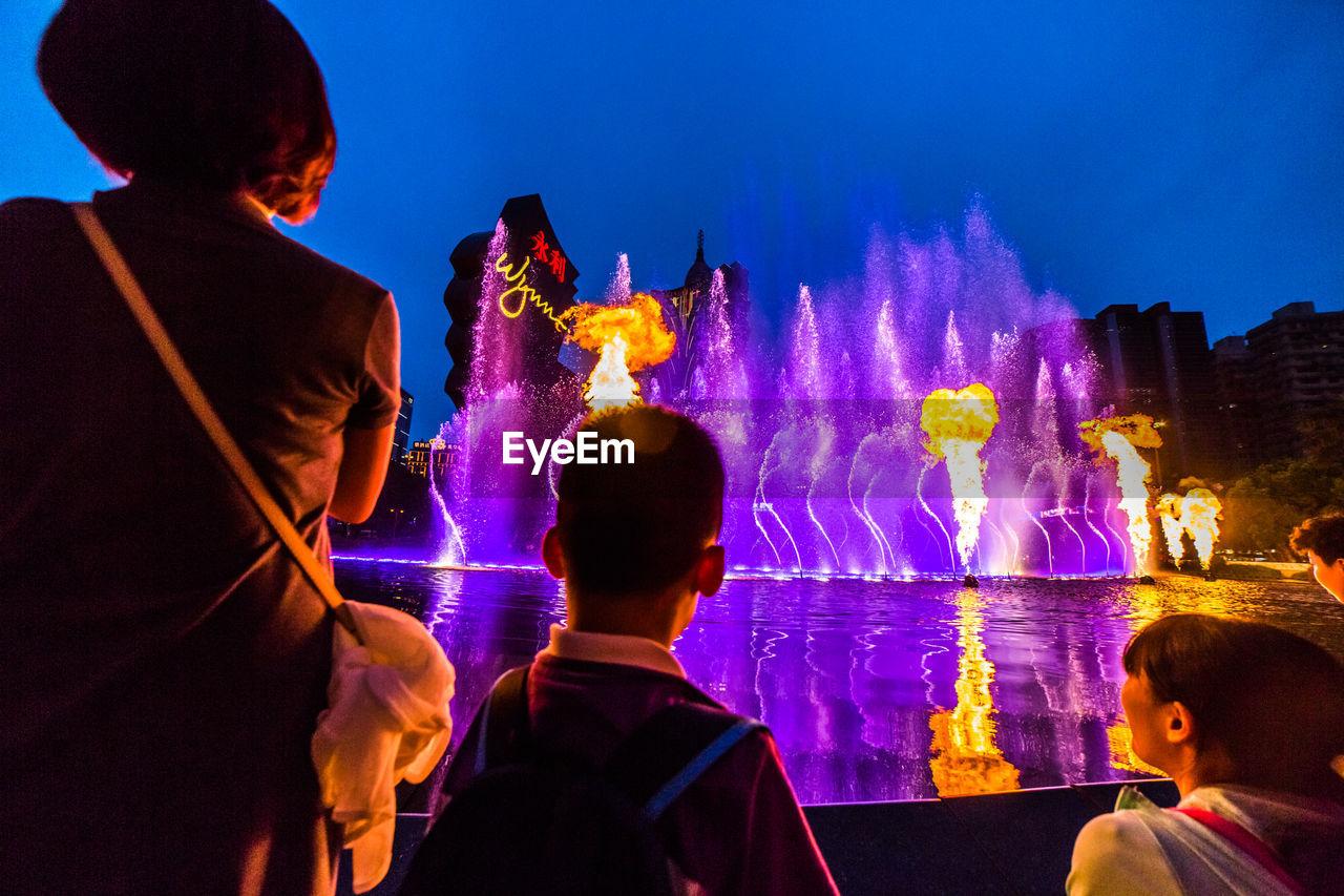 PEOPLE ENJOYING FOUNTAIN AT NIGHT