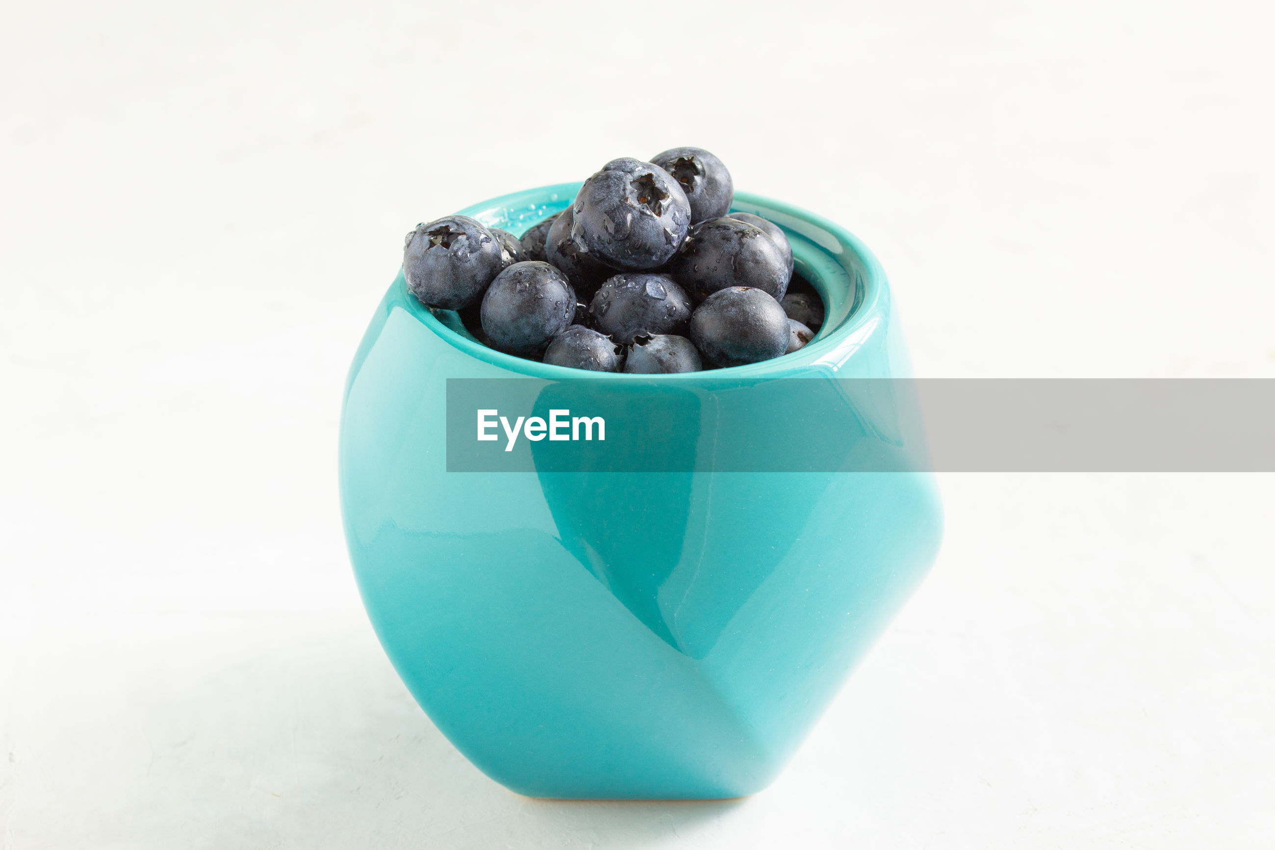 Blueberries in a turquoise pot on a light gray table. pot in the center of the image