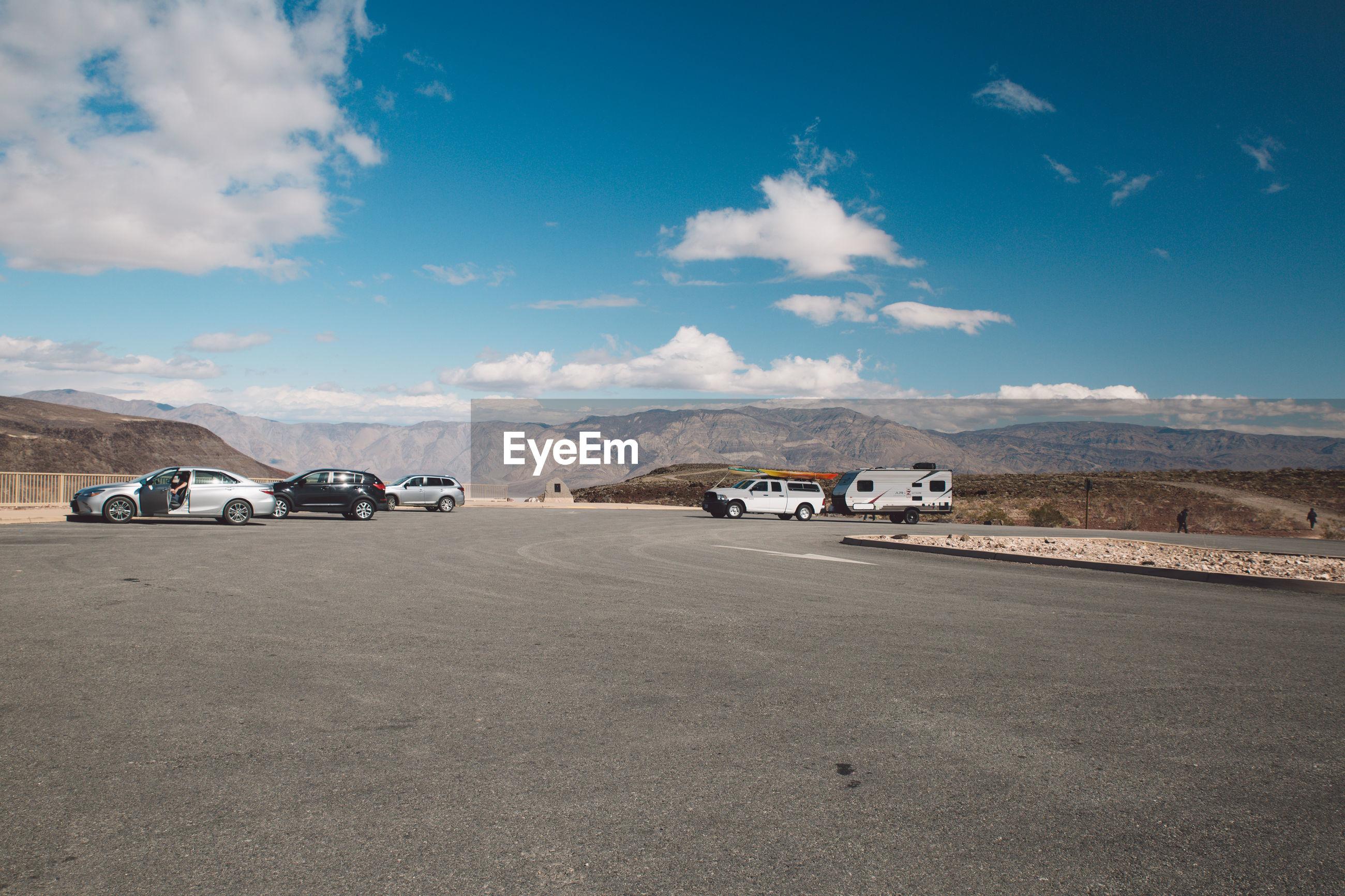CARS ON ROAD IN DESERT AGAINST SKY