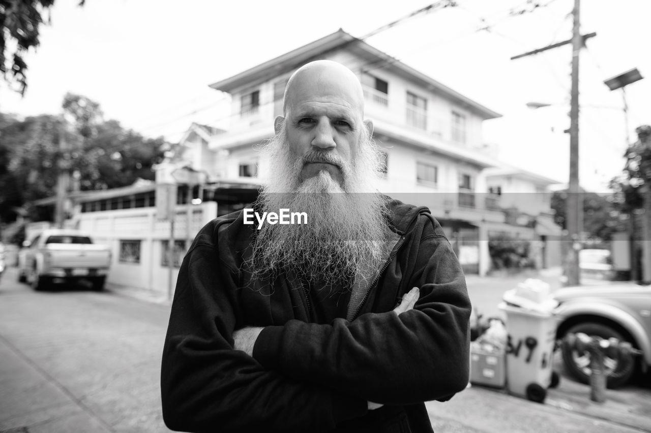 Portrait of man standing on street in city