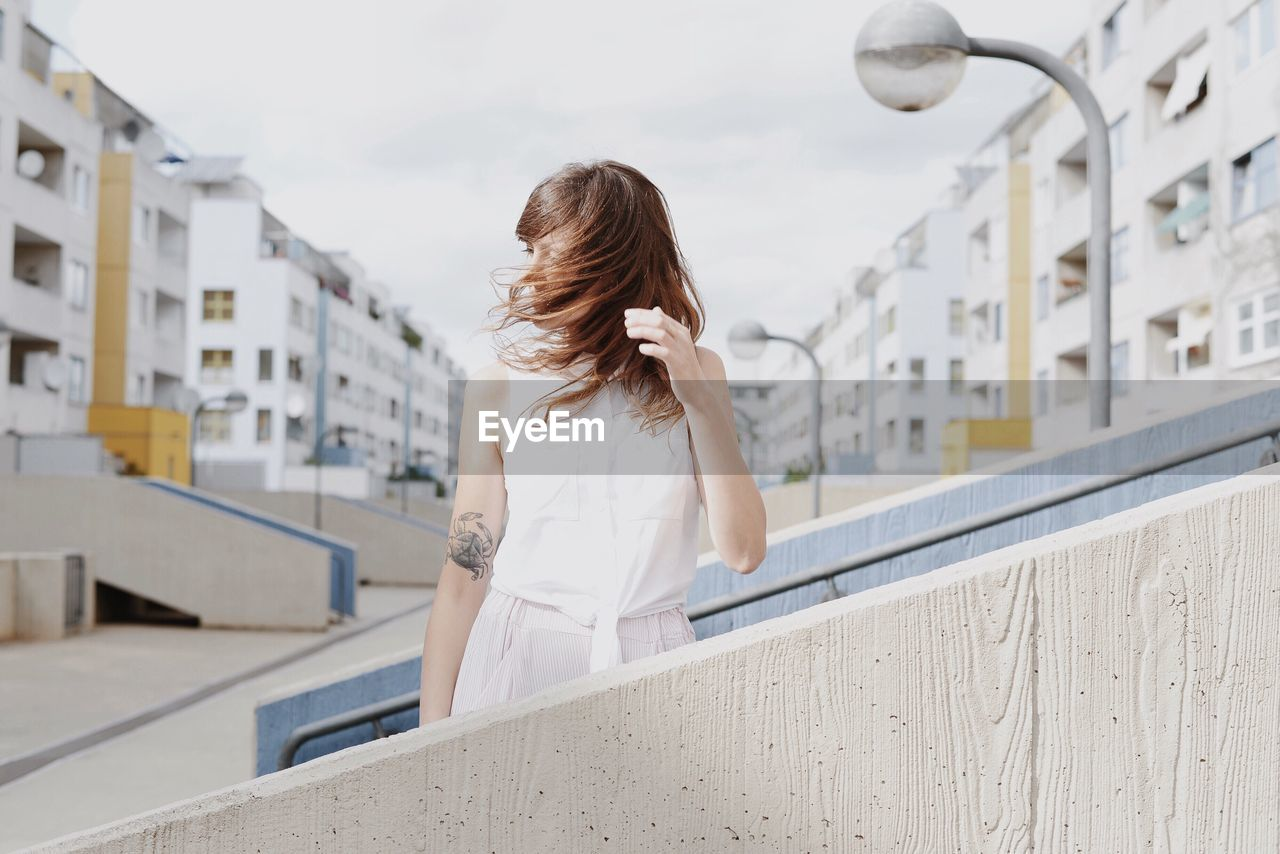 Young Woman Shaking Head While Standing By Railing On Steps Against Sky In City