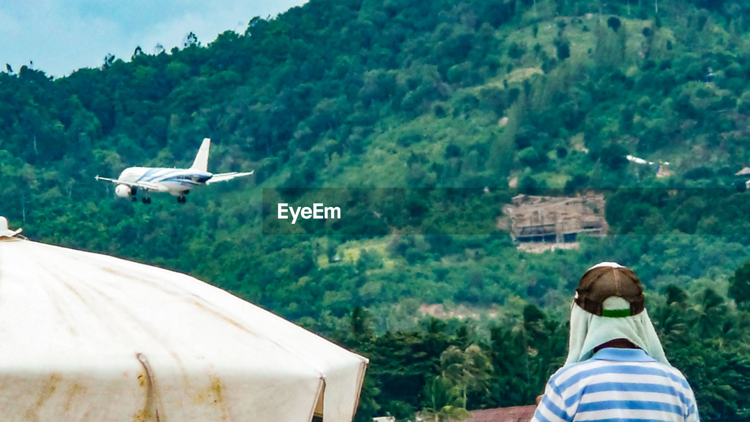 Rear view of man looking airplane flying by mountain