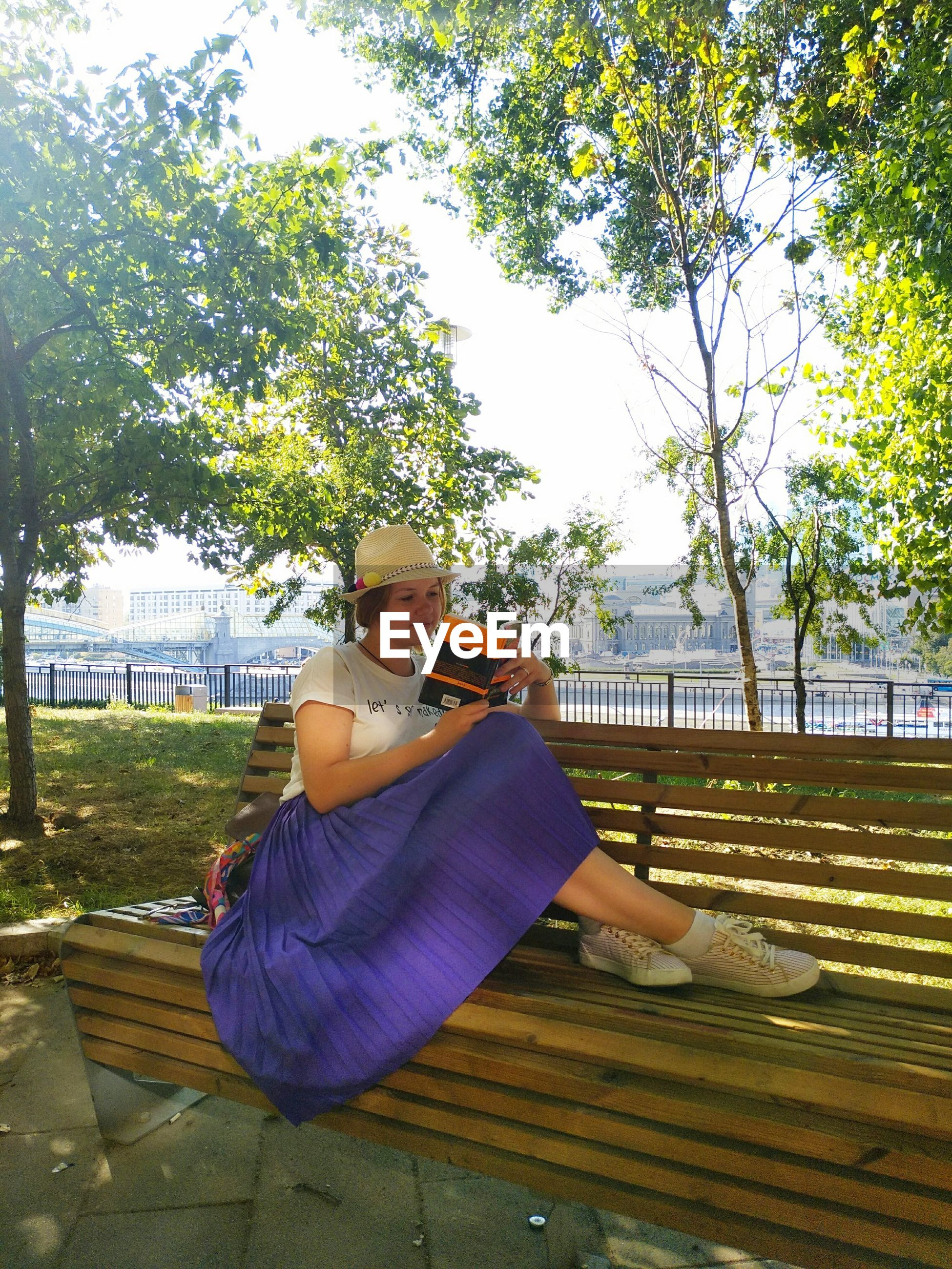 Woman reading book while sitting on bench in park