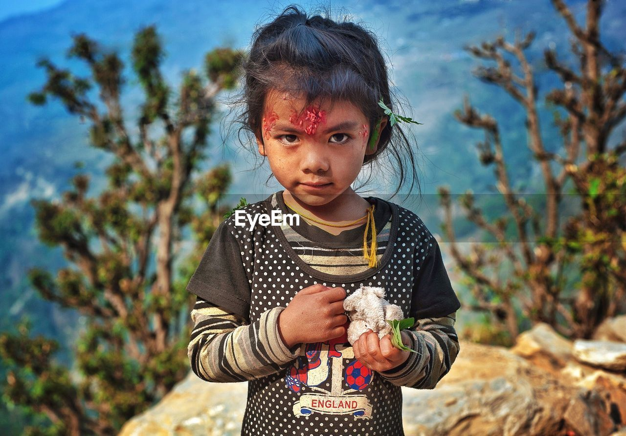 childhood, one person, looking at camera, portrait, focus on foreground, holding, child, outdoors, children only, standing, day, real people, nature, tree, people, close-up, sky, adult