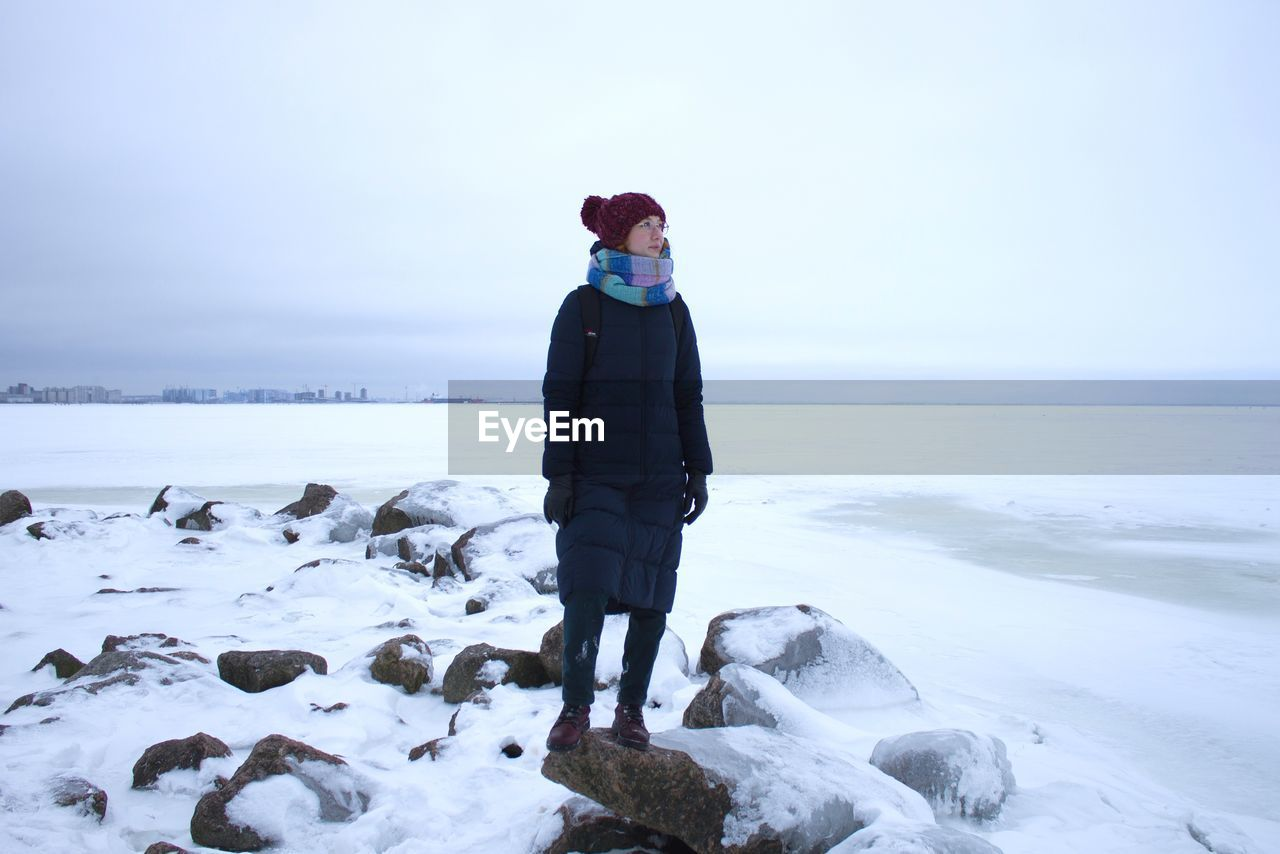 winter, cold temperature, one person, scenics - nature, full length, snow, sea, water, beauty in nature, real people, sky, standing, warm clothing, leisure activity, nature, land, clothing, lifestyles, horizon over water, outdoors