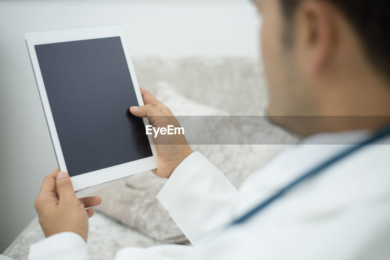 Midsection Of Doctor Holding Digital Tablet