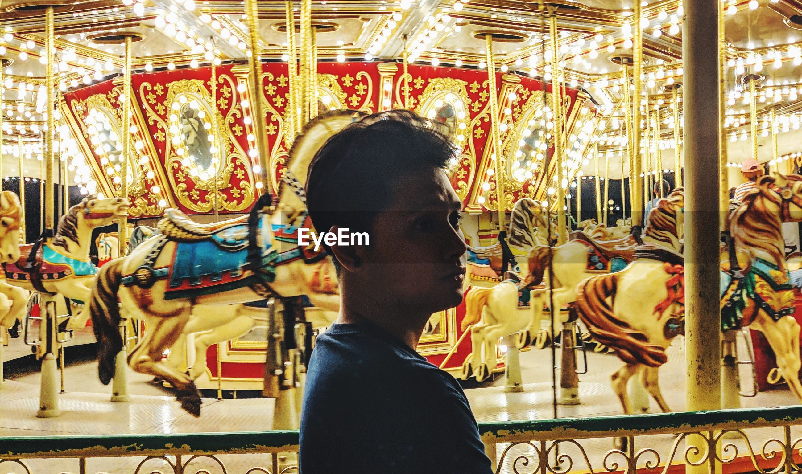 SIDE VIEW OF BOY LOOKING AT CAROUSEL