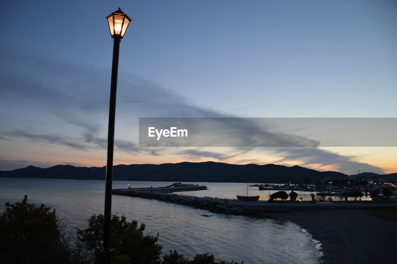 sky, water, mountain, street light, sunset, sea, nature, scenics, cloud - sky, beauty in nature, outdoors, no people, tranquil scene, tranquility, illuminated, mountain range, nautical vessel, tree, day