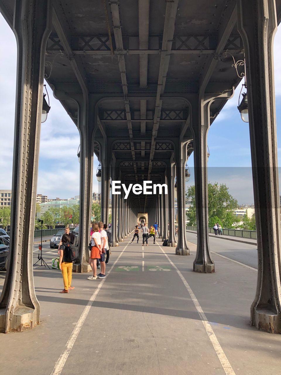 People under bridge in city