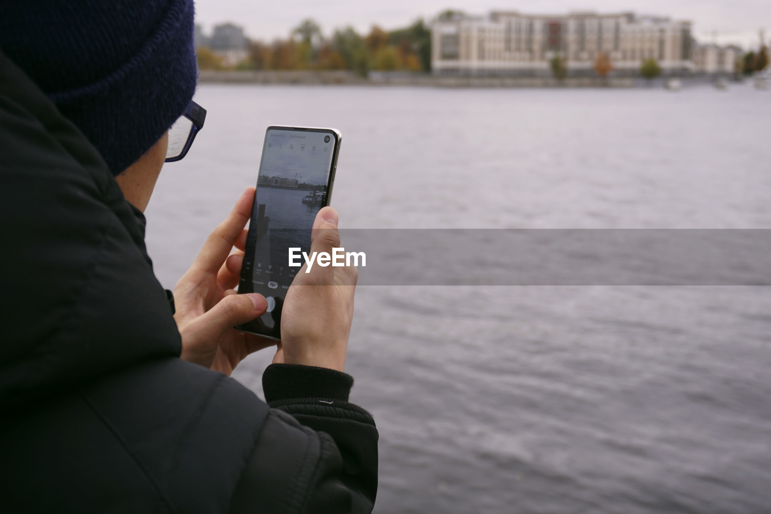 Midsection of man using mobile phone by river