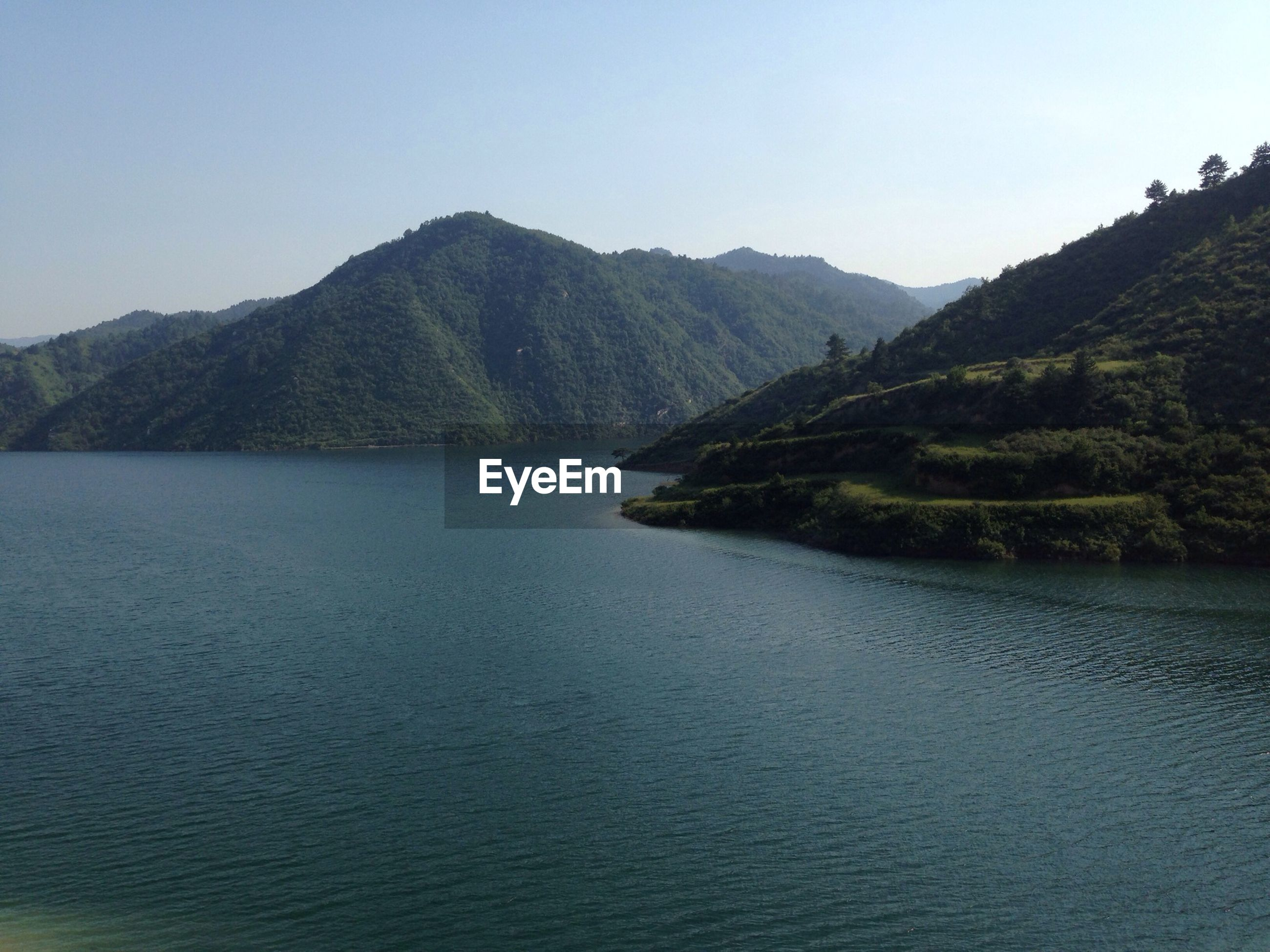 mountain, water, tranquil scene, clear sky, tranquility, scenics, mountain range, beauty in nature, waterfront, nature, lake, tree, rippled, river, idyllic, copy space, landscape, non-urban scene, hill, outdoors