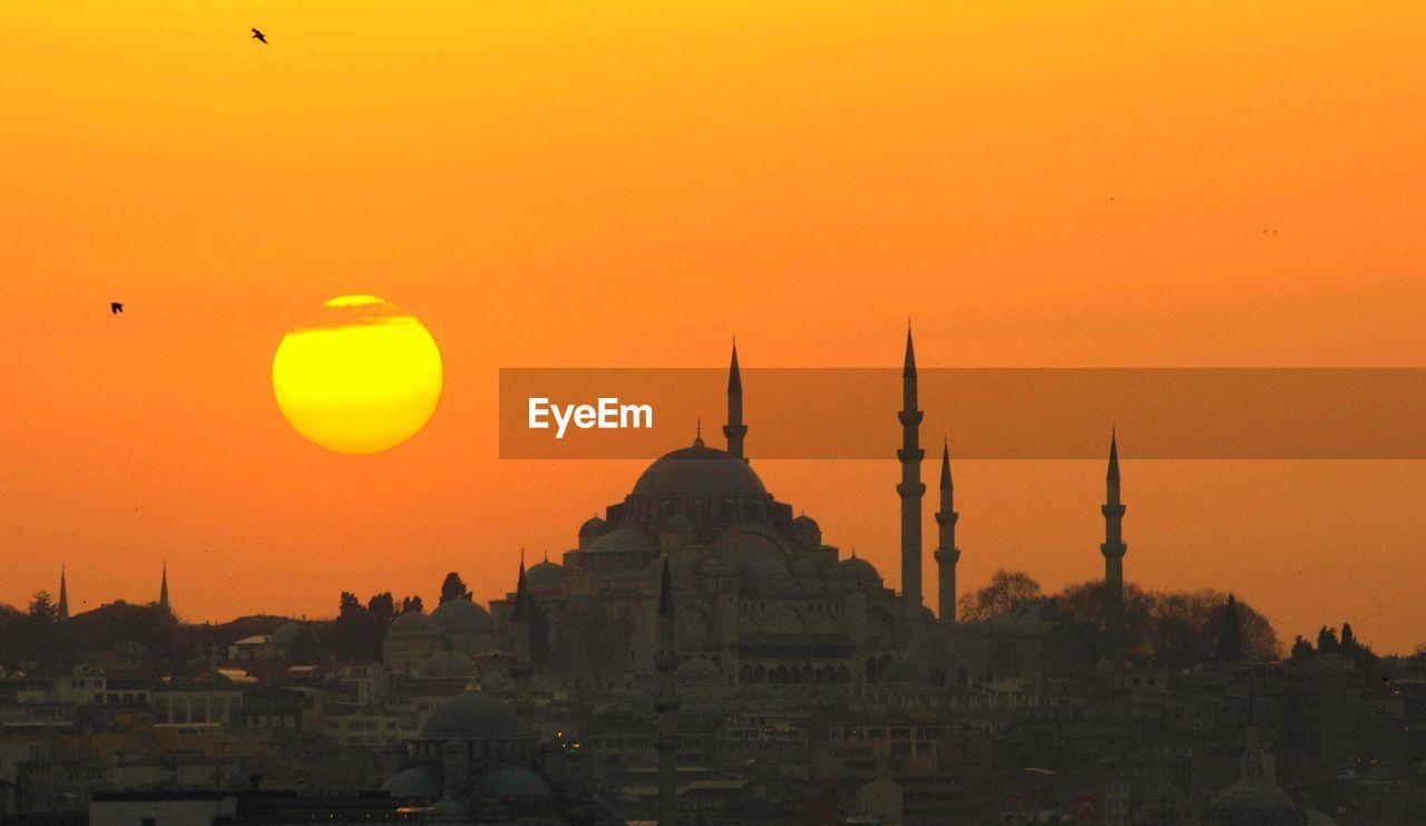 New Mosque In City Against Orange Sky