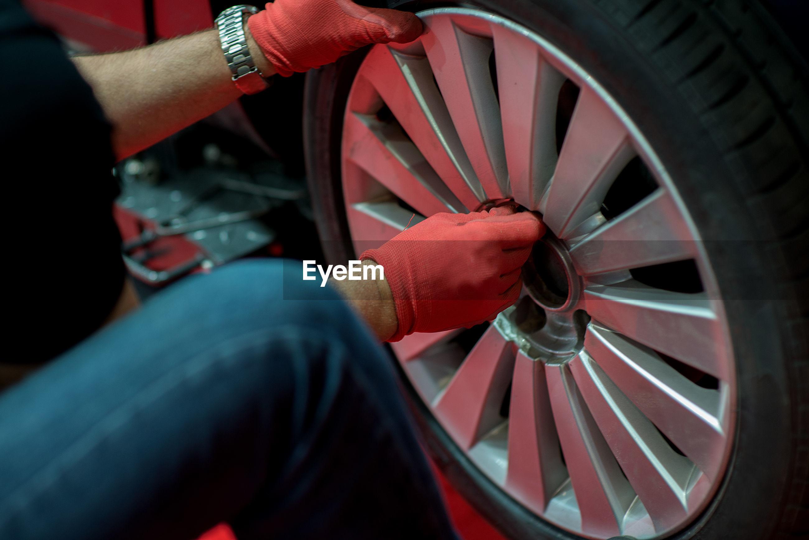 Midsection of mechanic repairing car wheel