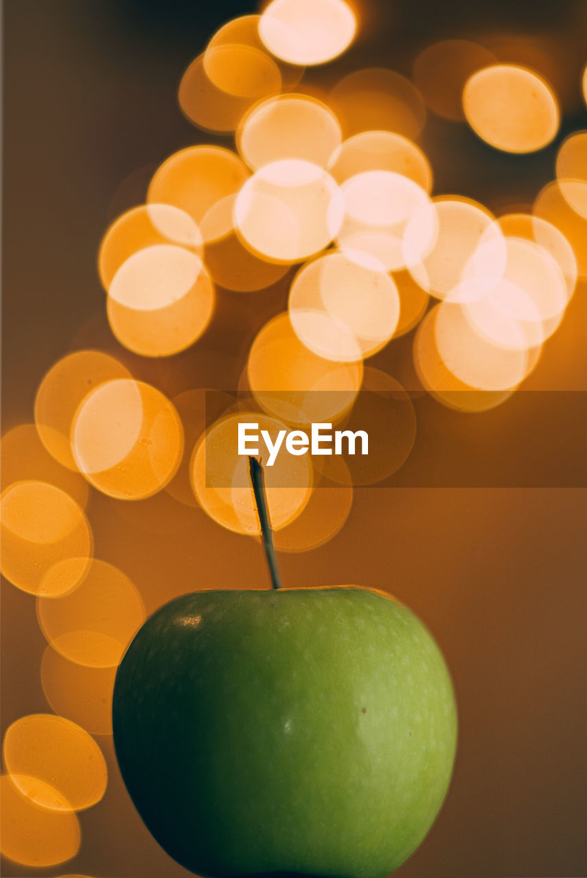 fruit, food and drink, healthy eating, apple - fruit, food, close-up, wellbeing, green color, freshness, indoors, illuminated, no people, apple, focus on foreground, still life, granny smith apple, glowing, table, studio shot, orange color