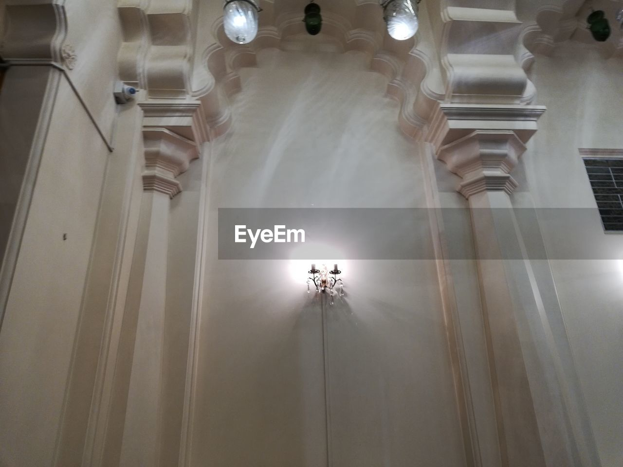 low angle view, illuminated, lighting equipment, architecture, indoors, built structure, ceiling, no people, hanging, electric light, light, electricity, building, chandelier, glowing, light beam, technology, white color, directly below, electric lamp