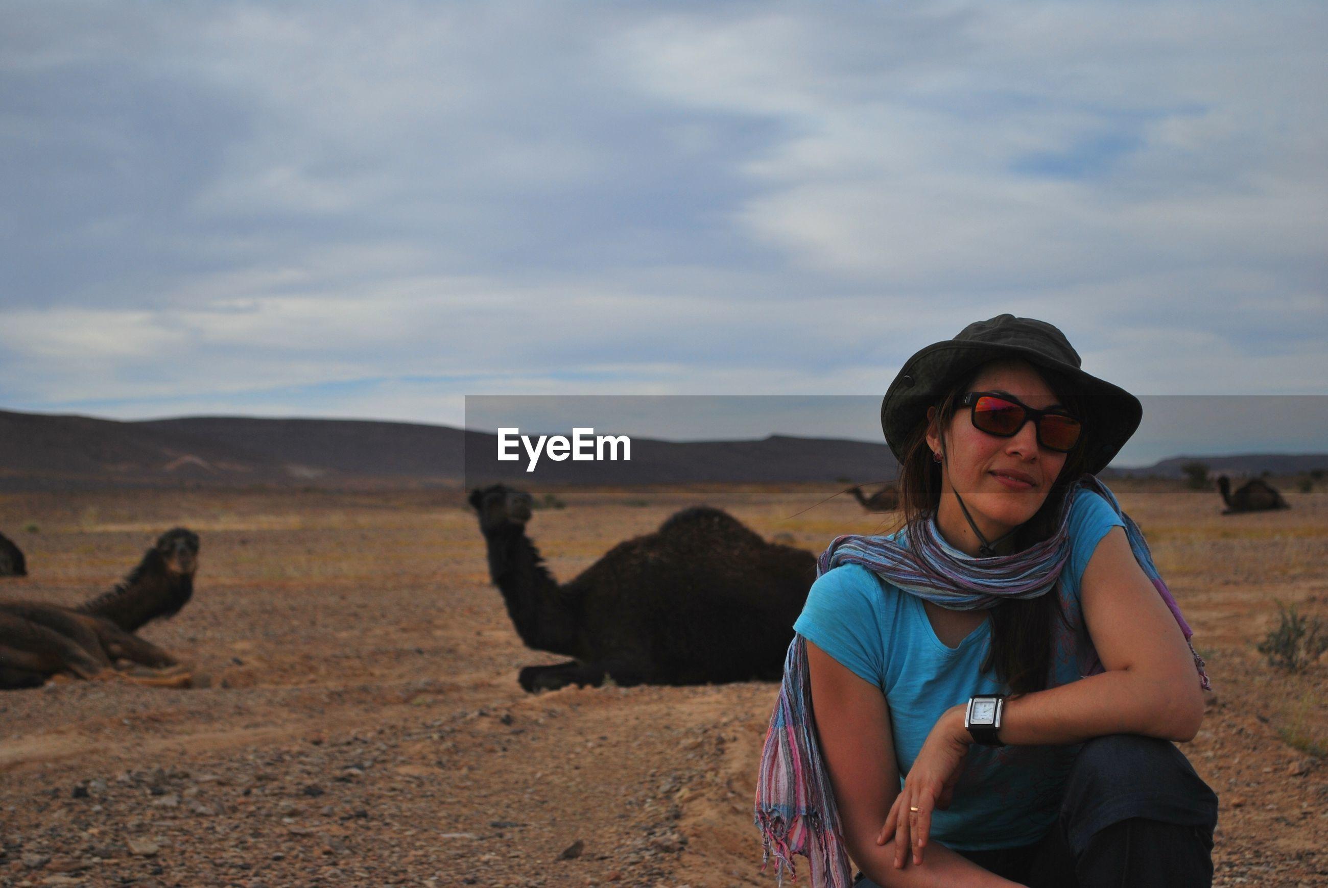 Portrait of woman in desert against sky