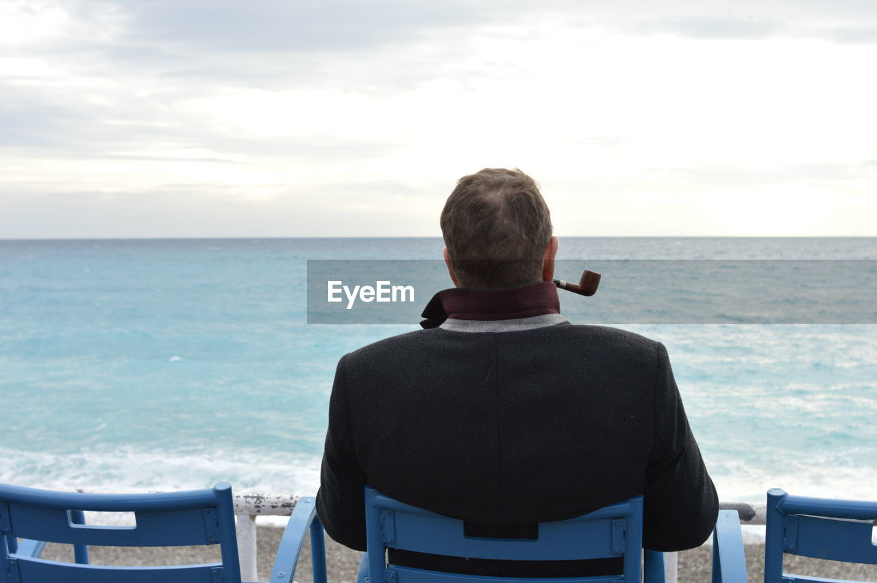 Rear View Of Man With Smoking Pipe Sitting By Sea Against Sky