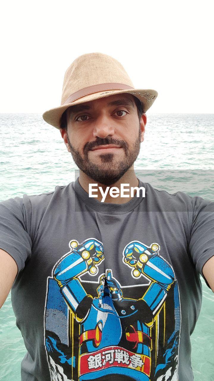PORTRAIT OF MATURE MAN AT BEACH