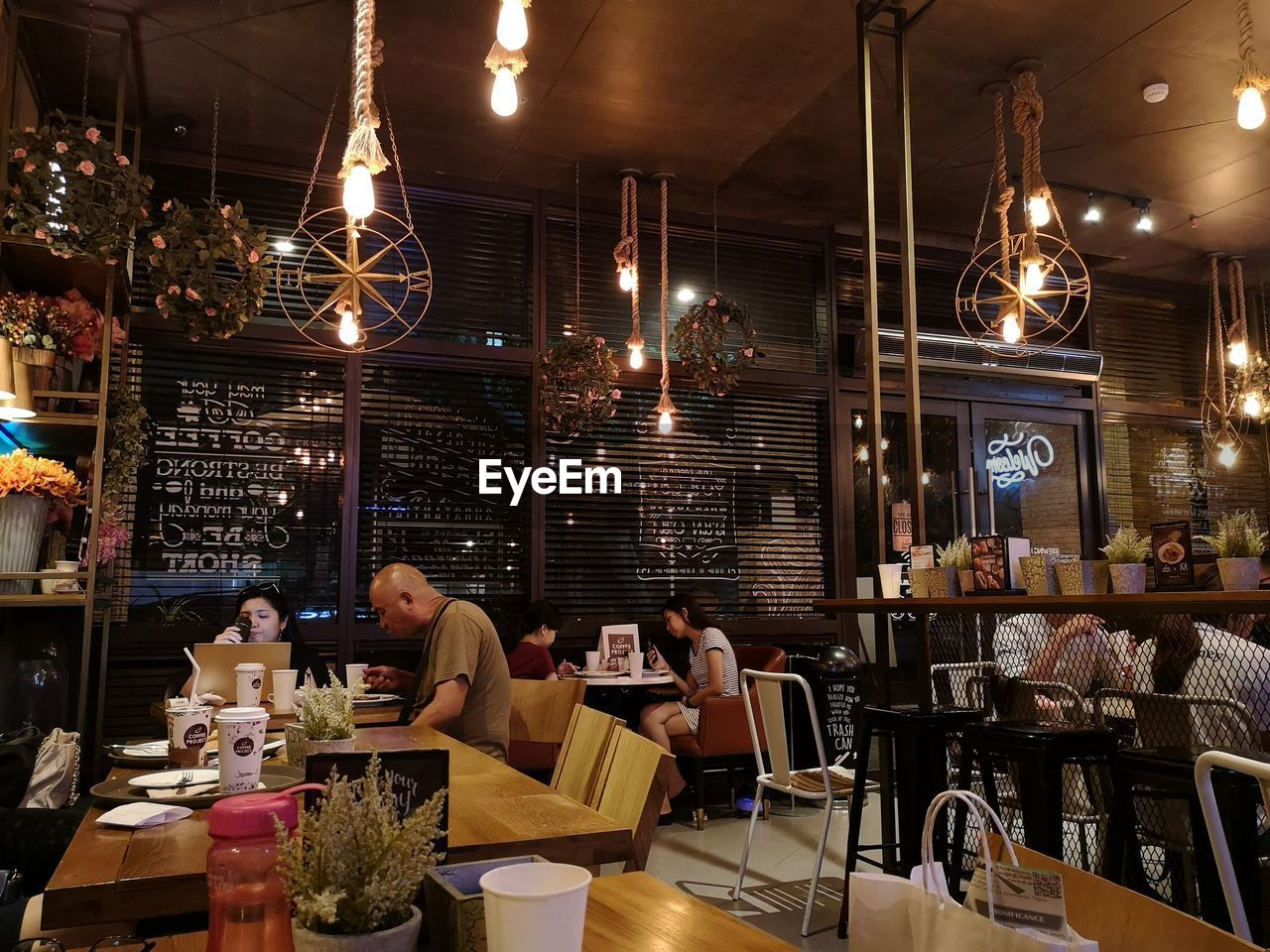 illuminated, restaurant, business, food and drink, real people, women, sitting, group of people, lighting equipment, table, adult, food, men, lifestyles, seat, food and drink industry, cafe, night, indoors, architecture