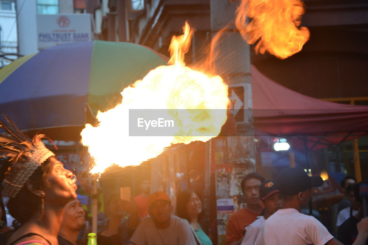 real people, burning, fire, flame, heat - temperature, fire - natural phenomenon, group of people, men, people, adult, women, night, lifestyles, architecture, glowing, crowd, incidental people, city, motion