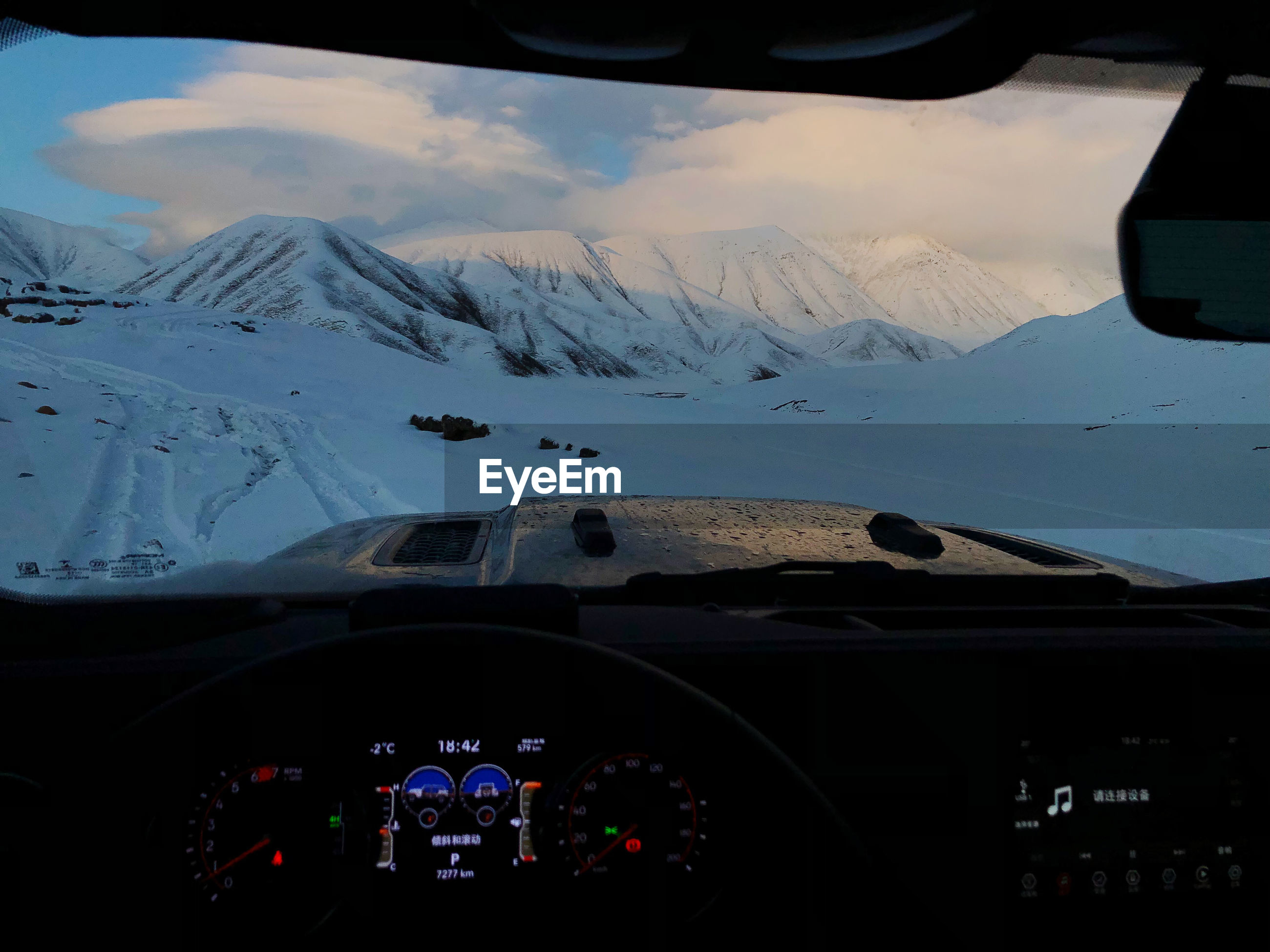 AERIAL VIEW OF SNOW COVERED MOUNTAINS SEEN THROUGH CAR WINDSHIELD