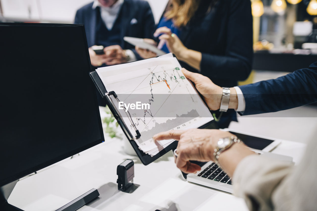 office, technology, business, computer, connection, businesswoman, wireless technology, business person, communication, adult, indoors, table, laptop, women, working, colleague, cooperation, holding, midsection, businessman, teamwork, using laptop, coworker