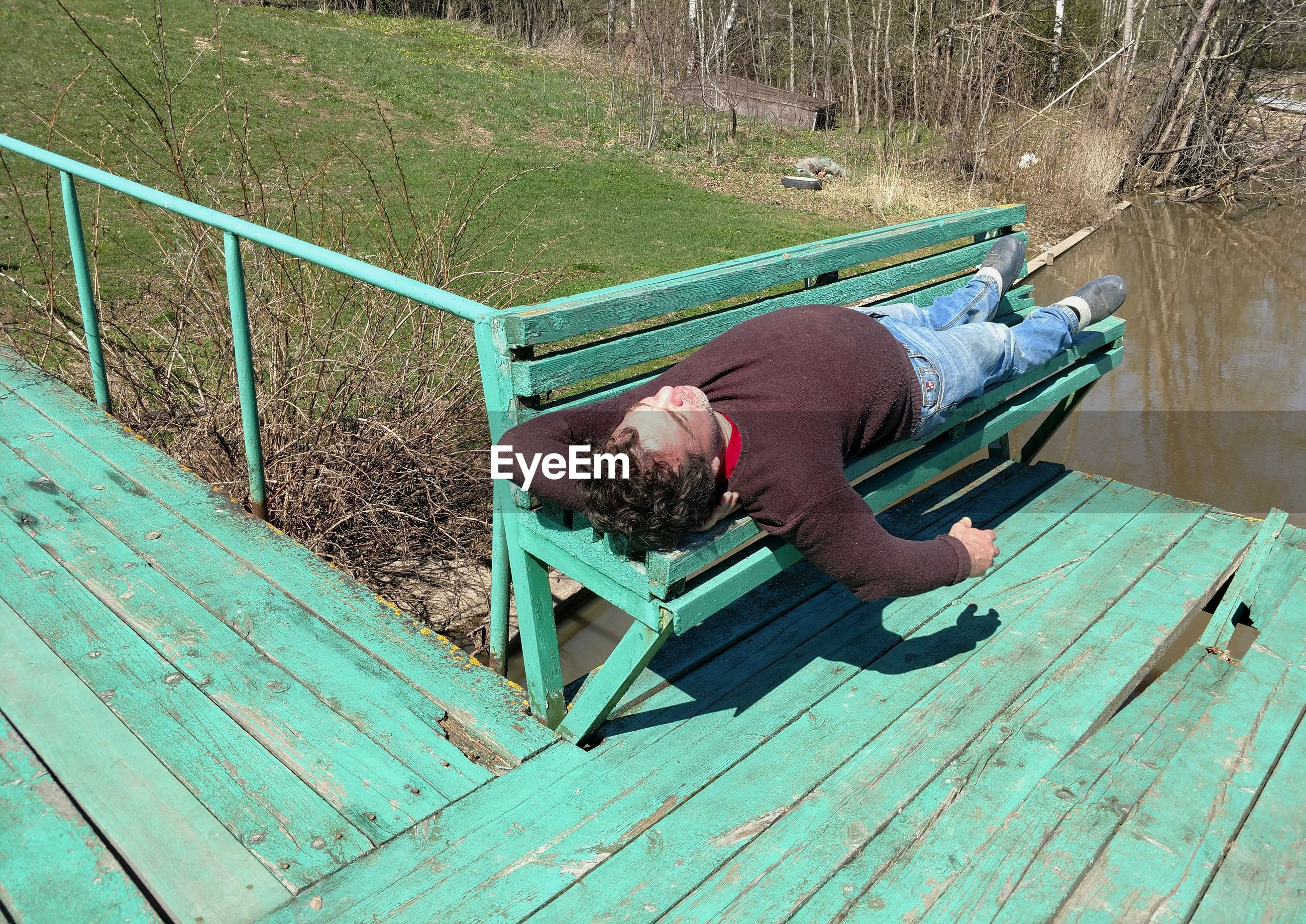 High angle view of man lying on bench by lake