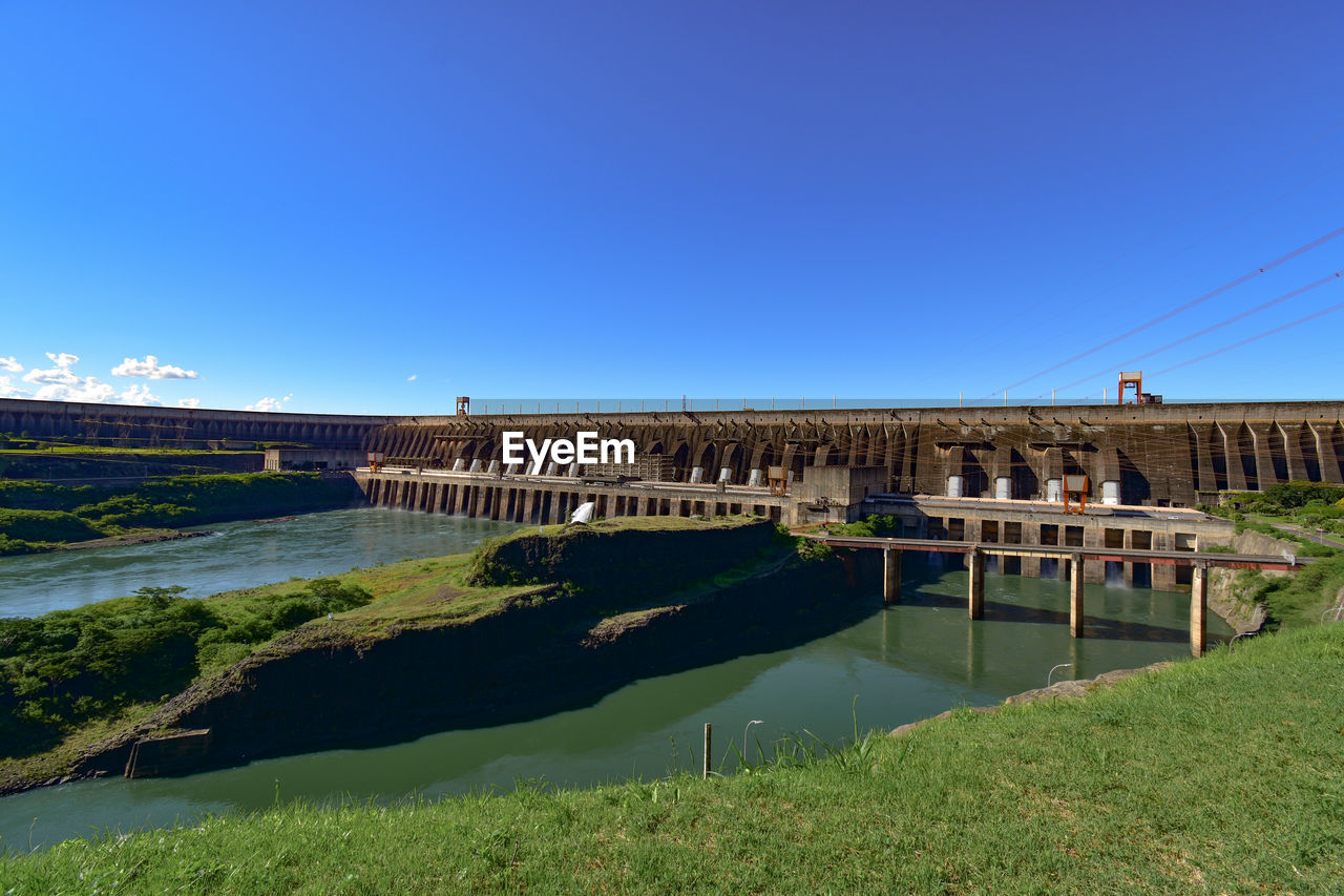 View of bridge over canal against clear blue sky
