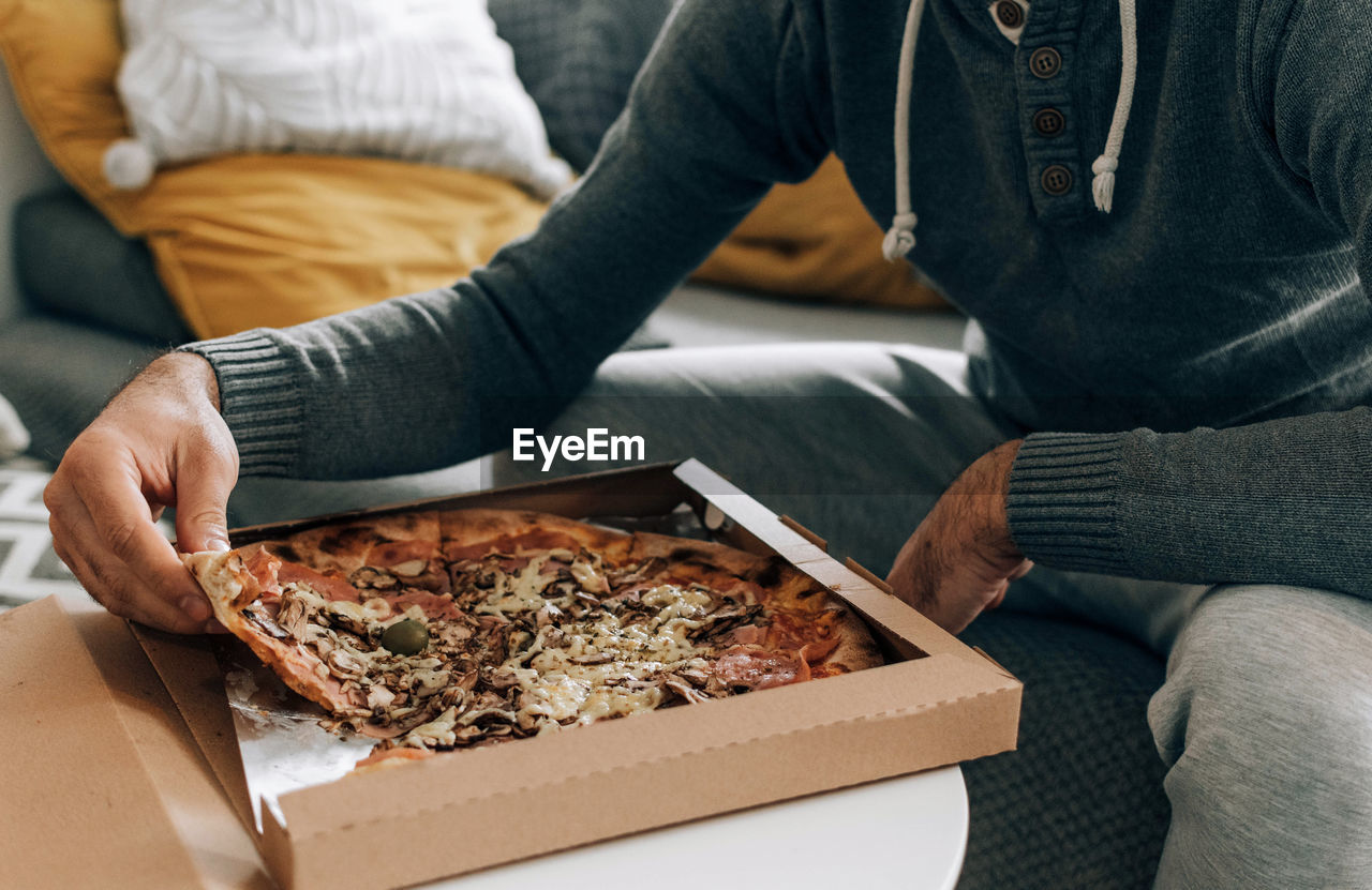 Man sitting on couch, eating pizza. pizza box, pizza delivery.